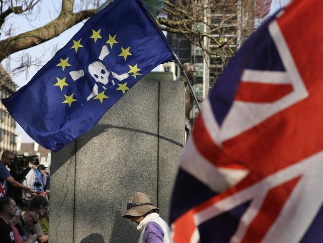 Pro-Brexit protesters wave flags in Parliament Square at the end of the 'March to Leave' in London on March 29. Picture: Matt Dunham/AP
