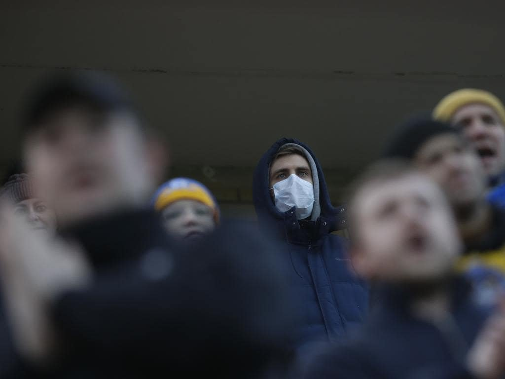 Football fans of FC Bate, one of them wearing a face mask, watch the Belarus Championship soccer match between Energetik-BGU and Bate in Minsk, Belarus.